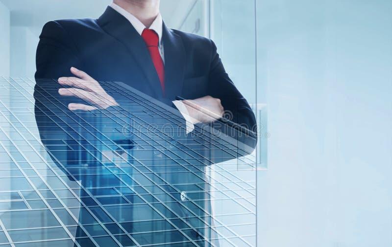 Exposición doble, Empresario con brazo cruzado y modernos edificios de oficinas interiores imagen de archivo