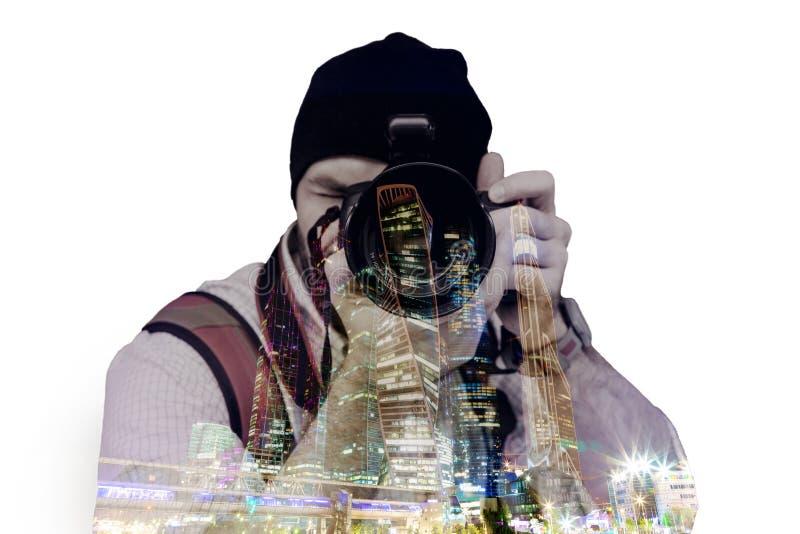 Exposición doble, un hombre que toma fotografía y la ciudad grande moderna en el fondo de la noche imagenes de archivo