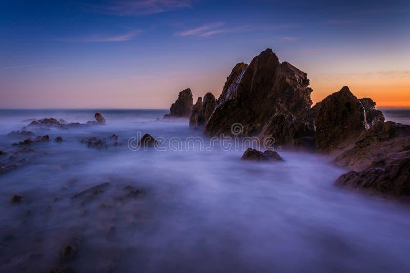 Exposición larga de las ondas que se estrellan en rocas en la puesta del sol fotografía de archivo