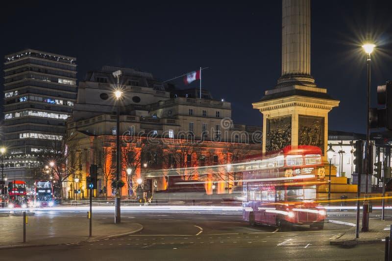 Exposición larga de Trafalgar Square con un autobús inglés típico del autobús de dos pisos fotografía de archivo