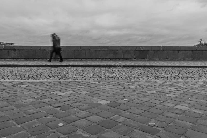 Exposición larga de un peatón que camina en un puente en un día lluvioso fotografía de archivo libre de regalías