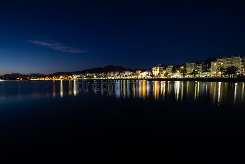 Exposición larga de una costa costa en la noche sobre el mar con las luces de la ciudad fotos de archivo libres de regalías