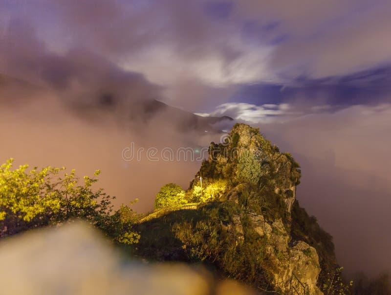 Exposición larga de una roca en las montañas francesas, encendida por la luna y una farola imagen de archivo libre de regalías