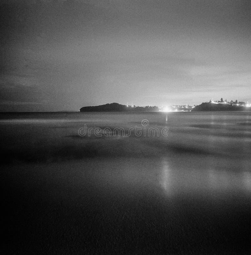 Exposición larga del océano de la noche con las luces de la ciudad en el analo monocromático de la película del formato del cuadr imágenes de archivo libres de regalías