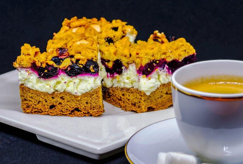Expositie van cake met de witte room van Aronia op witte die plaat dichtbij kop van koffie met suiker op zwarte achtergrond wordt royalty-vrije stock foto