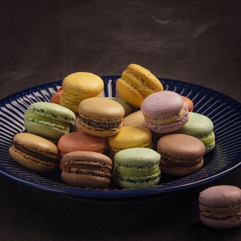 Exposition of colorful and tasty macaron candy, many colors yellow, green, brown, pink in blue plate. royalty free stock photo