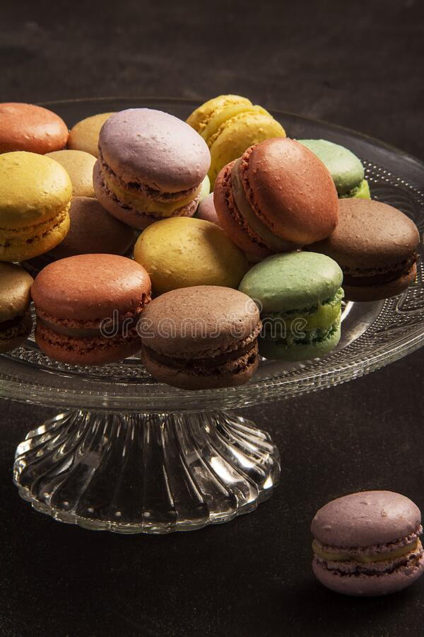 Exposition of colorful and tasty macaron candy, many colors yellow, green, brown, pink in blue plate. royalty free stock images
