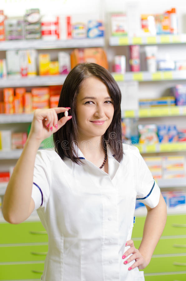 Exposition de femme de chimiste de pharmacien une pilule La pharmacie de pharmacie est fond Assez, jeune laborant image libre de droits