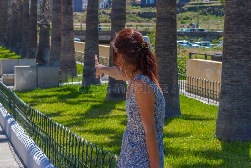 Exposition de jeune femme quelque chose par le doigt en parc Vue par derrière et arrière images libres de droits