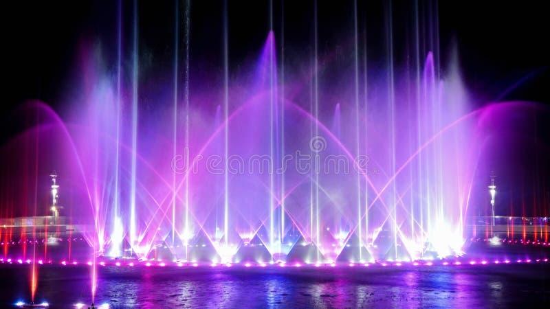 Exposition de musique lumineuse par danse colorée de fontaine contre la nuit foncée photographie stock libre de droits