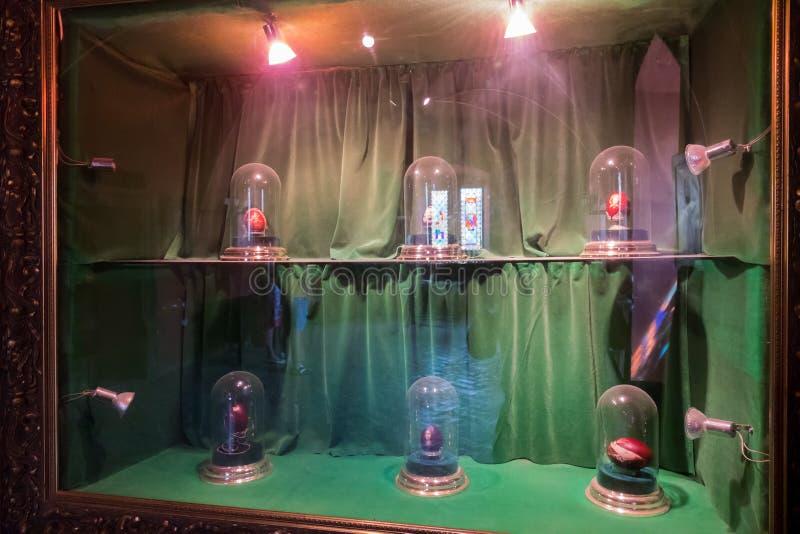 Exposition des oeufs peints sous les chapeaux en verre sur des étagères sur un fond vert avec le contre-jour dans un cadre exposi photographie stock