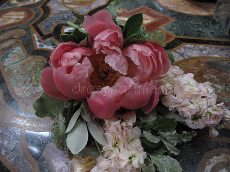Exposition Pink peony with greens. On the marble table stock image