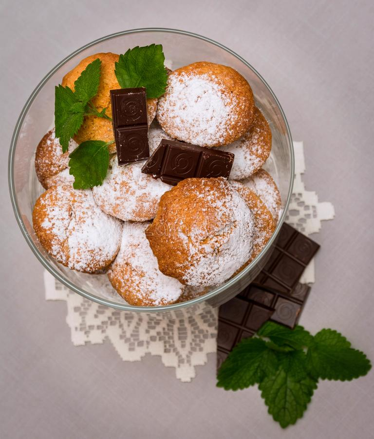 Exposition of tasty cake with chocolate and banana inside in big vase ont table, chocolate bars and mint near vase. cupcake. Exposition of tasty cake with stock image