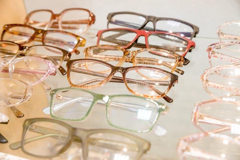 Expositor de los vidrios que consisten en los estantes de los vidrios de moda mostrados en una pared en la tienda óptica la óptic foto de archivo libre de regalías
