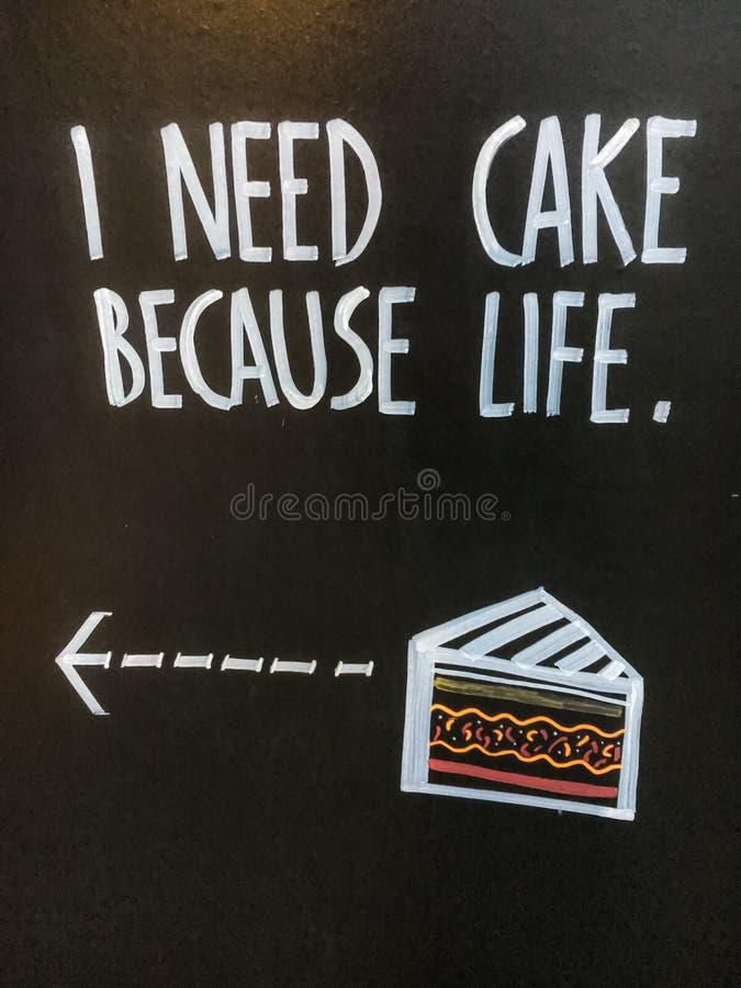 Expréseme 'necesitan la torta porque vida 'en la publicidad del tablero negro en la calle foto de archivo libre de regalías
