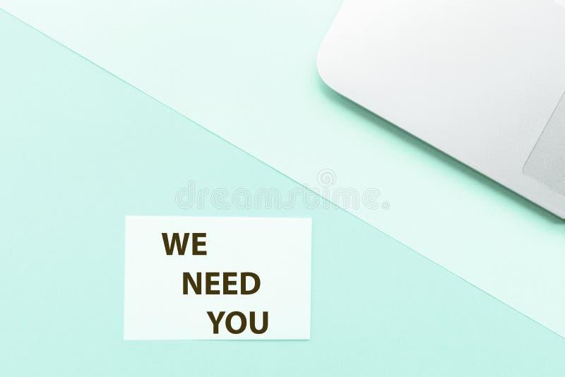 Exprésenos necesitan le y el ordenador portátil en fondo verde Visi?n superior Maqueta, espacio de la copia Aviso del reclutamien imagen de archivo libre de regalías