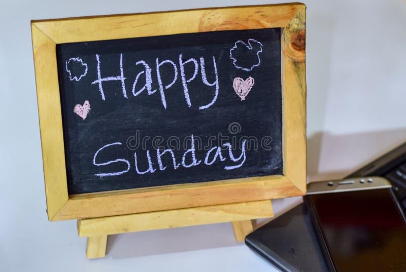 Exprese domingo feliz escrito en una pizarra en ella y el smartphone, ordenador portátil fotos de archivo libres de regalías