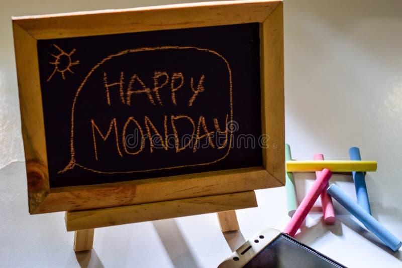 Exprese lunes feliz escrito en una pizarra en ella y el smartphone, tiza colorida fotos de archivo libres de regalías