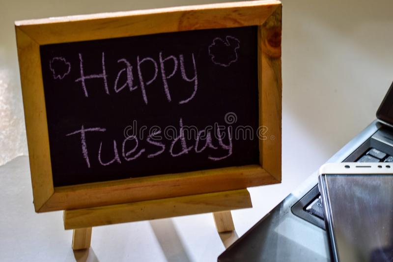 Exprese martes feliz escrito en una pizarra en ella y el smartphone, ordenador portátil fotografía de archivo