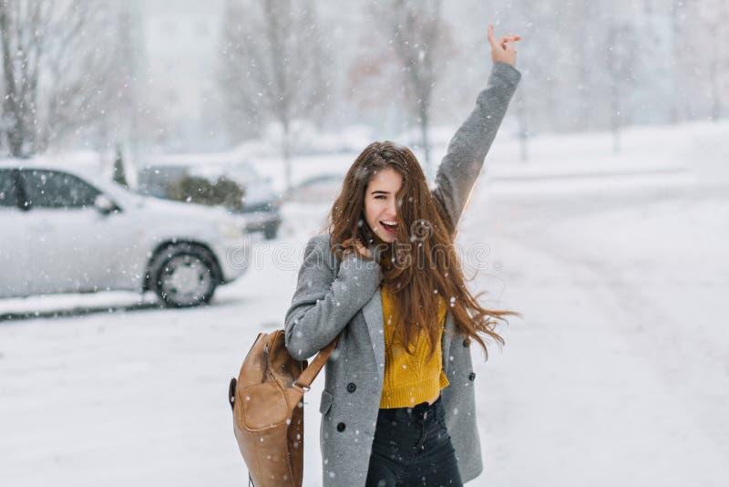 Expresión de las emociones verdaderas positivas felices de la muchacha que caminan en tiempo que nieva en invierno en la calle El fotos de archivo