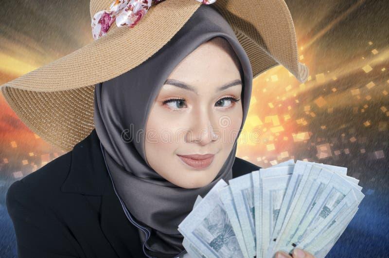 Expresión extraña de la mujer joven mientras que sostiene el billete de banco sobre fondo abstracto imagen de archivo libre de regalías