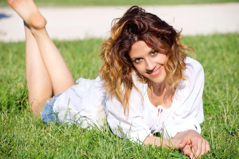 Expresión intensa de la mujer hermosa que mira la mentira sonriente de la cámara en parque imágenes de archivo libres de regalías