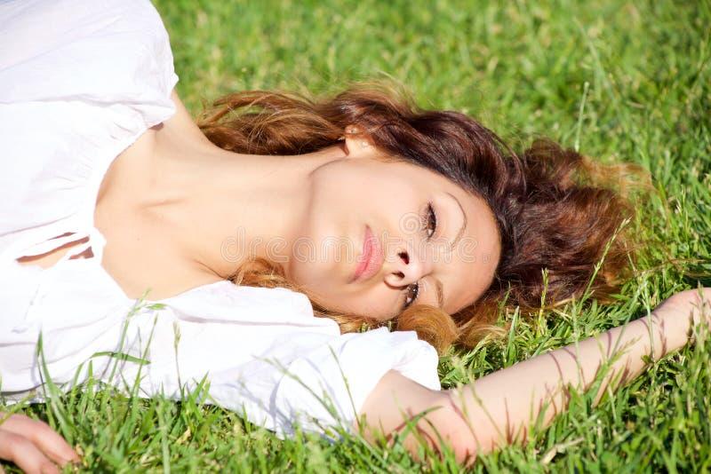 Expresión intensa de la mujer hermosa que mira la mentira sonriente de la cámara en primer del parque imagen de archivo