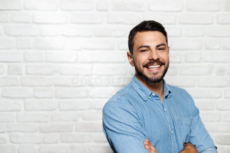 Expresiones faciales del hombre joven de la barba en la pared de ladrillo fotografía de archivo