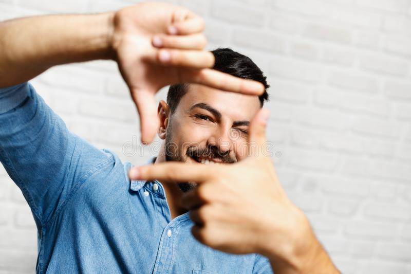 Expresiones faciales del hombre joven de la barba en la pared de ladrillo imagen de archivo