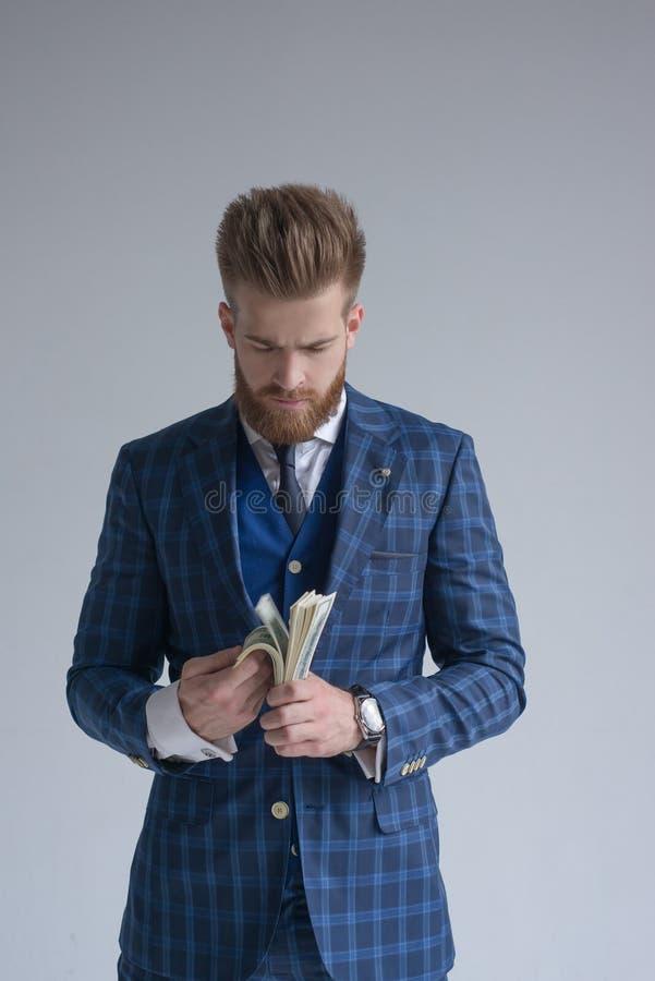 Expresiones - hombre de negocios hermoso de los jóvenes en traje y lazo que cuenta el dinero Aislado en fondo gris fotografía de archivo