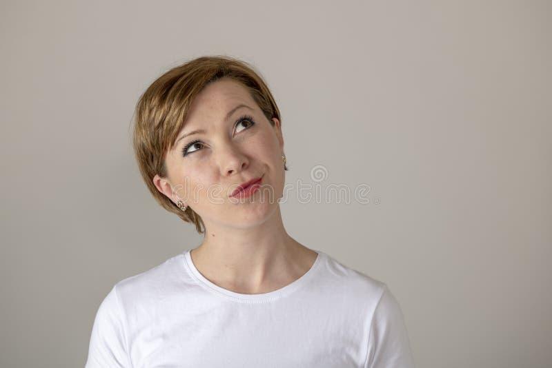 Expresiones y emociones humanas mujer atractiva joven con un pensamiento y la mirada para arriba que se pregunta fotos de archivo