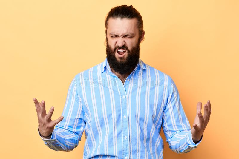 Expresive bearded man expresses negative emotion on a yellow background. royalty free stock photography