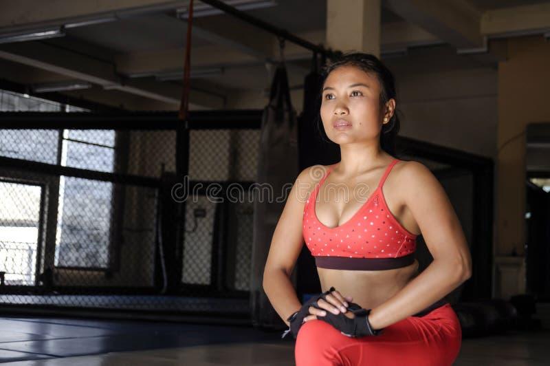 A expressão concentrada da cara da mulher asiática suado nova no esporte veste o esticão dos pés que relaxam os músculos no gym foto de stock royalty free