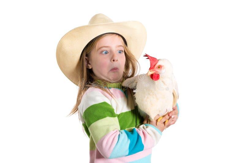 A expressão engraçada da menina da criança surpreendeu o gesto assustado da galinha imagem de stock