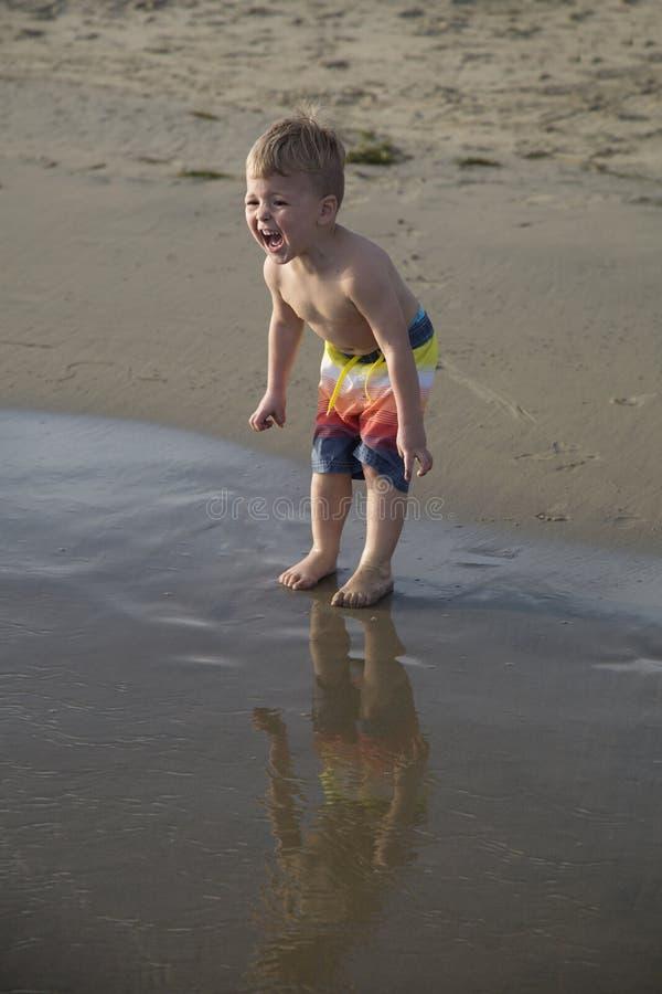 Expressão facial feliz do menino querido na praia que está no fotos de stock royalty free