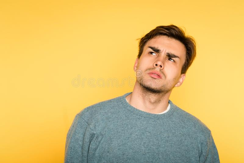 A expressão hesitante duvidoso duvidosa do homem olha acima foto de stock