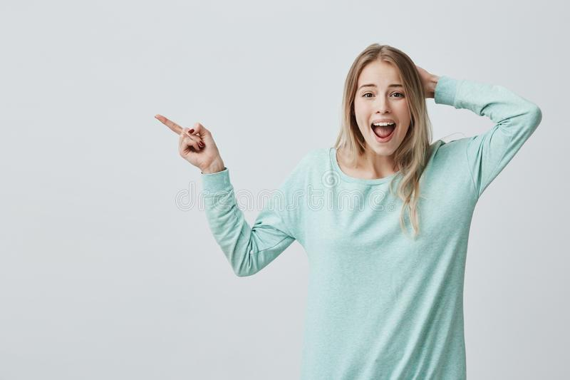 Expressões, emoções e sentimentos do rosto humano Astonished chocou a fêmea loura nova na roupa ocasional que aponta com imagens de stock royalty free