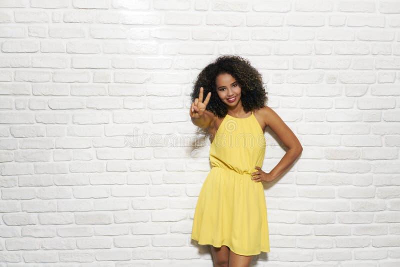 Expressões faciais da mulher negra nova na parede de tijolo fotografia de stock