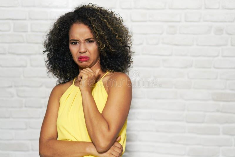 Expressões faciais da mulher negra nova na parede de tijolo fotos de stock royalty free