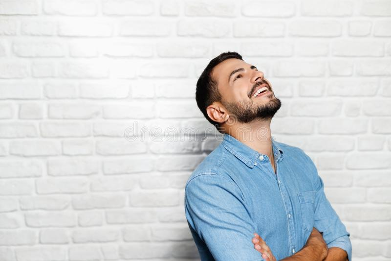 Expressões faciais do homem novo da barba na parede de tijolo fotografia de stock