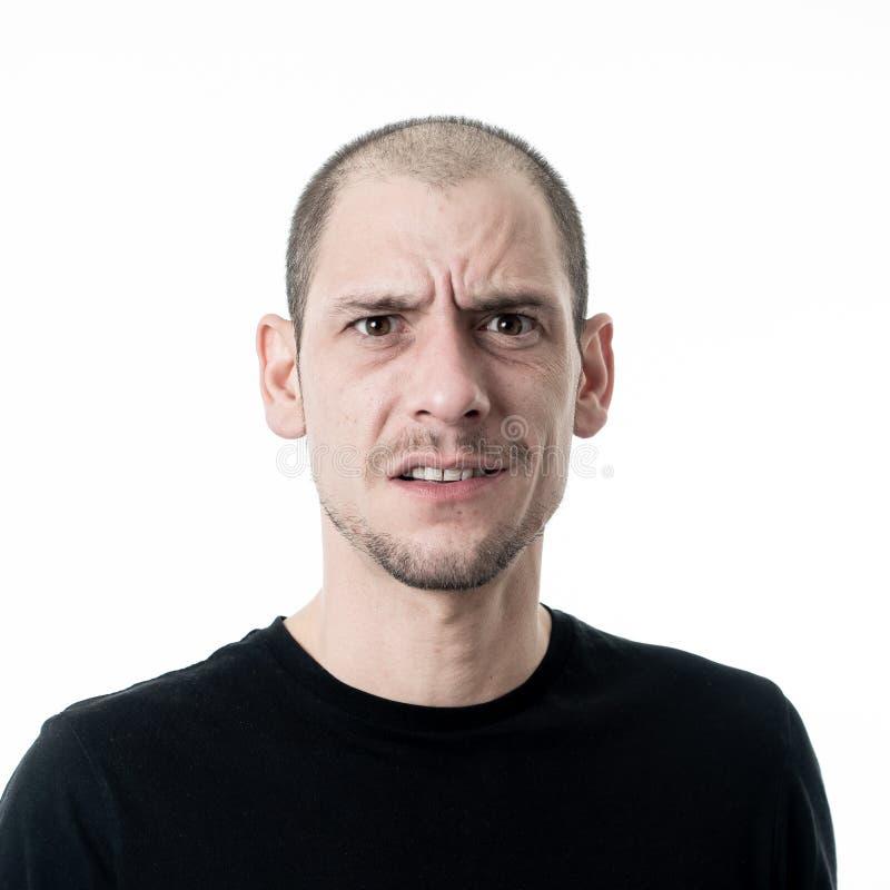 Expressões faciais e emoções humanas Retrato de homem novo confuso que pensa e que olha confundido imagens de stock royalty free