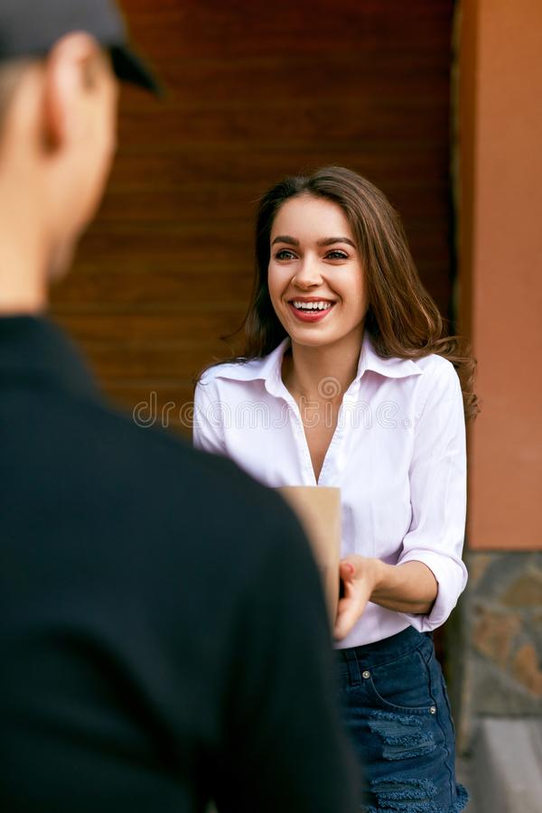 Express Delivery Service. Courier Delivering Package To Woman. Express Delivery Service. Courier Man Delivering Package To Woman Outdoors. High Resolution stock photo