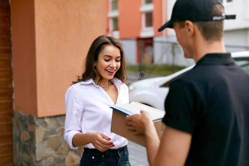 Express Delivery Service. Courier Delivering Package To Woman. Express Delivery Service. Courier Man Delivering Package To Woman Outdoors. High Resolution royalty free stock photos