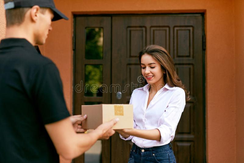 Express Delivery Service. Courier Delivering Package To Woman. Express Delivery Service. Courier Man Delivering Package To Woman Outdoors. High Resolution stock photos