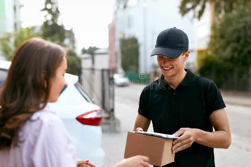 Express Delivery Service. Courier Delivering Package To Woman. Express Delivery Service. Courier Man Delivering Package To Woman Outdoors. High Resolution royalty free stock image