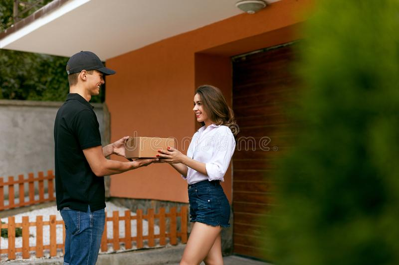 Express Delivery Service. Courier Delivering Package To Woman. Express Delivery Service. Courier Man Delivering Package To Woman Outdoors. High Resolution stock photography