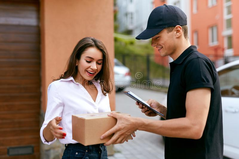Express Delivery Service. Courier Delivering Package To Woman. Express Delivery Service. Courier Man Delivering Package To Woman Outdoors. High Resolution royalty free stock photo