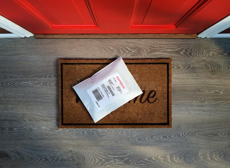 Express envelope package delivered to residential front door. Expedited padded express envelope delivered on doormat outside residential front door. Overhead royalty free stock image
