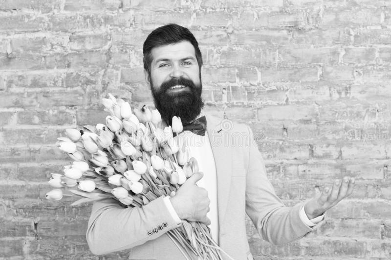 Express positivity. happy womens day. Flower for March 8. Spring gift. happy bearded man hipster with flowers, copy. Space. Bearded happy man with tulip bouquet royalty free stock photo