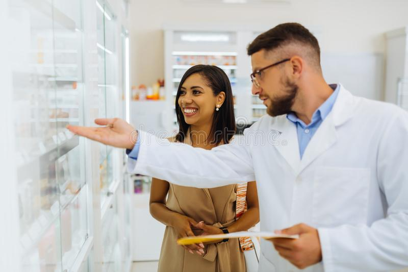 Happy young female person listening to pharmacist stock images